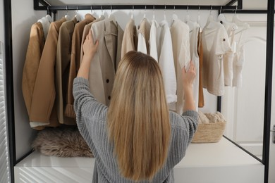 Young woman choosing outfit in dressing room, back view