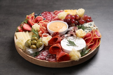 Wooden plate with different delicious snacks on grey table, closeup