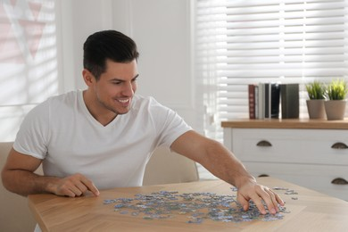 Man playing with puzzles at wooden table indoors