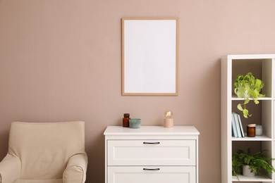 Empty frame hanging on pale rose wall over chest of drawers in living room. Mockup for design