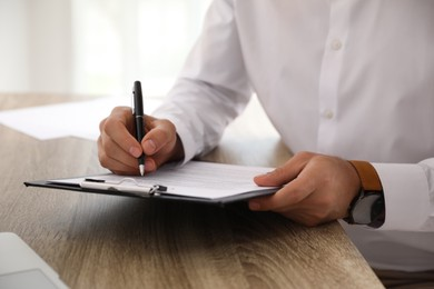 Businessman signing document at table indoors, closeup