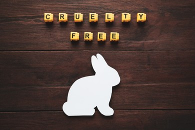 Cubes with text Cruelty Free and figure of rabbit on wooden table, flat lay. Stop animal tests
