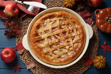 Delicious homemade apple pie and autumn decor on blue wooden table, flat lay. Thanksgiving Day celebration
