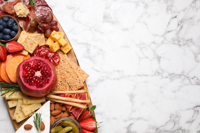 Wooden plate with different delicious snacks on white marble table, top view. Space for text