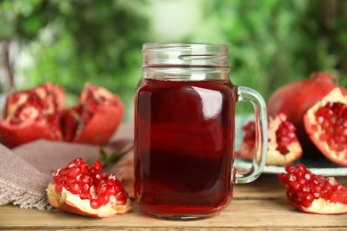 Pomegranate juice in mason jar and fresh fruits on wooden table outdoors