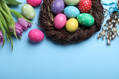 Flat lay composition with bright painted eggs on light blue background, space for text. Happy Easter