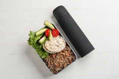 Thermos and lunch box with food on white wooden background, flat lay