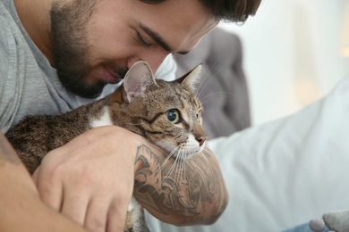 Happy man with cat on bed at home. Friendly pet