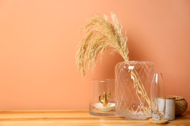 Vase with spikelets and decoration on wooden table near brown wall. Interior design