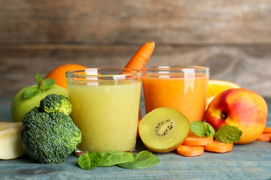 Glasses of delicious juices and fresh ingredients on blue wooden table