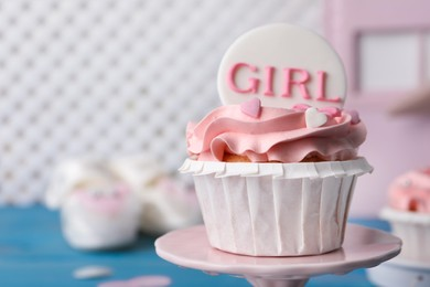 Delicious cupcake with pink cream and Girl topper for baby shower on stand, closeup