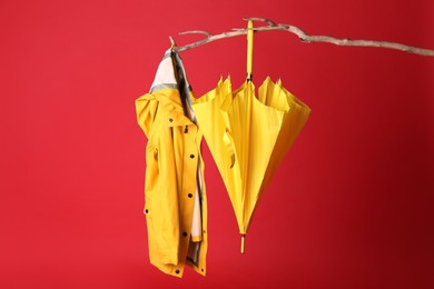 Closed yellow umbrella and stylish raincoat hanging on branch against red background