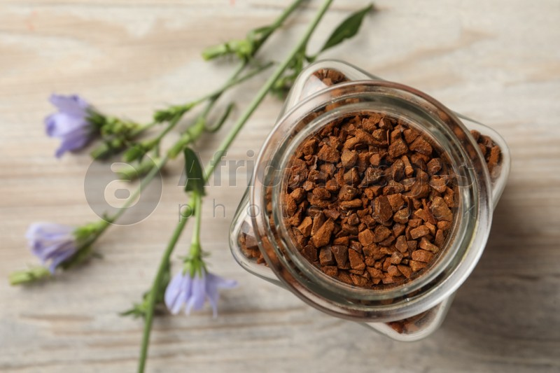 Jar of chicory granules on white wooden table, top view. Space for text