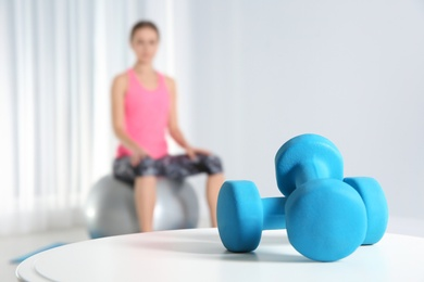 Dumbbells on table and woman doing fitness exercises at home. Space for text