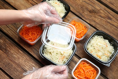 Waiter in gloves closing containers with salads at wooden table, closeup. Food delivery service