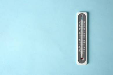 Weather thermometer on light blue background, top view. Space for text