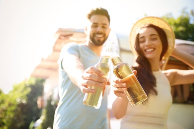 Young couple with bottles of beer outdoors, focus on hands. Camping season