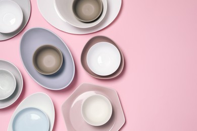 Different plates and bowls on pink background, flat lay. Space for text