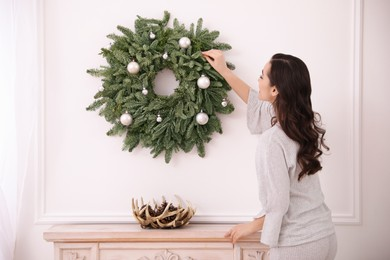 Young woman decorating Christmas wreath at home