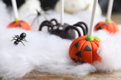 Different Halloween themed cake pops on wooden table, closeup