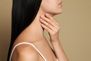 Young woman doing thyroid self examination on beige background, closeup