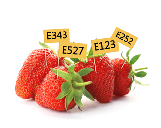 Ripe strawberries with E numbers on white background. Harmful food additives