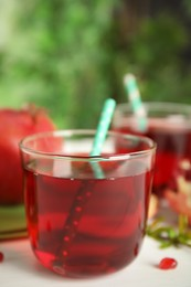 Pomegranate juice and fresh fruits on white table outdoors