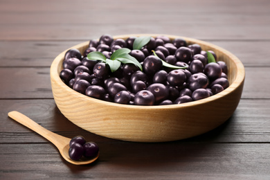 Tasty acai berries in bowl and spoon on wooden table, closeup