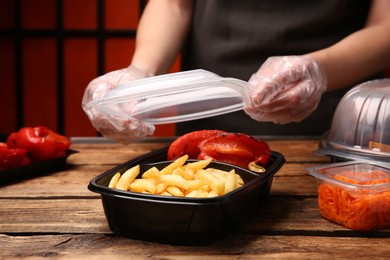 Waiter in gloves closing container with fresh prepared meal at wooden table, closeup. Food delivery service