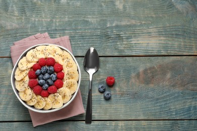 Tasty breakfast dish with berries, banana and chia seeds served on wooden table, flat lay. Space for text