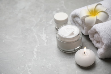Composition with towels and skin care products on light grey marble background, space for text