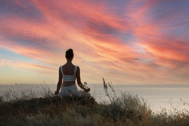 Woman meditating on hill near sea, back view. Space for text