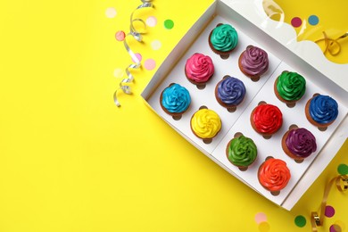 Box with different cupcakes and confetti on yellow background, flat lay. Space for text