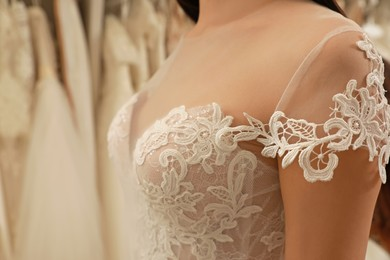 Woman trying on wedding dress in boutique, closeup