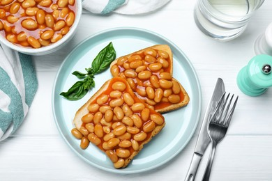 Toasts with delicious canned beans on white wooden table, flat lay
