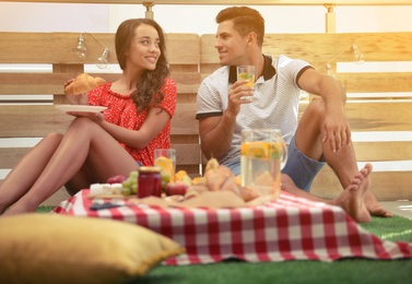 Happy couple with tasty snacks imitating picnic at home