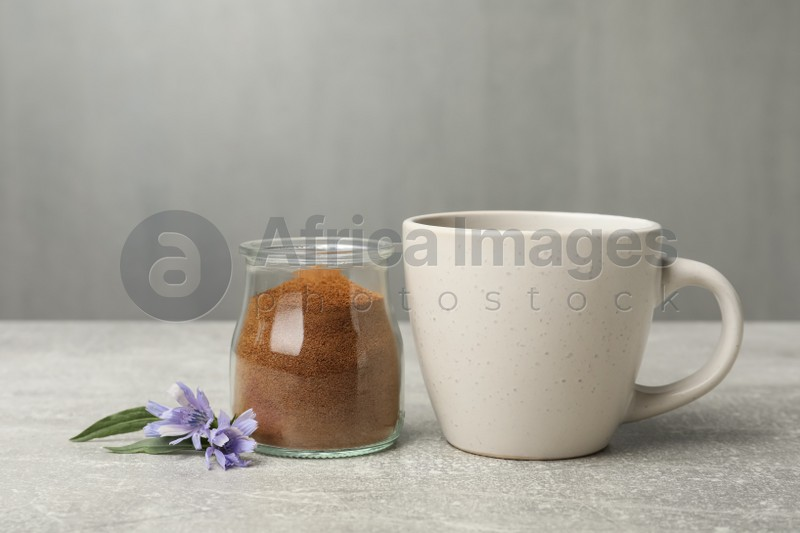 Jar with chicory powder, cup and flowers on light grey table