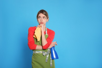 Young housewife with detergent and rag on light blue background. Space for text