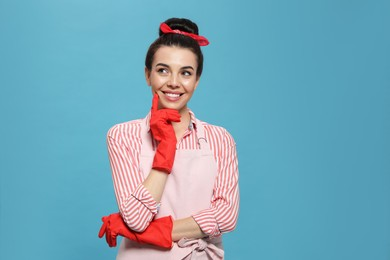 Housewife wearing rubber gloves on light blue background