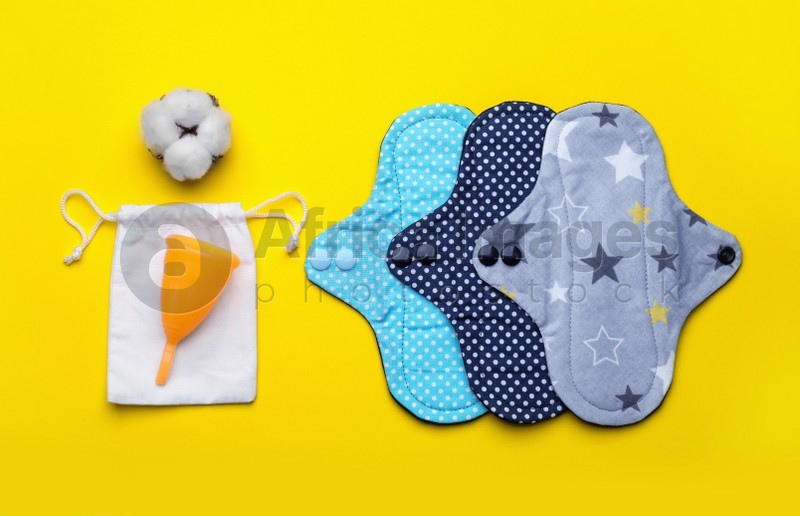 Reusable cloth pads, menstrual cup and cotton flower on yellow background, flat lay
