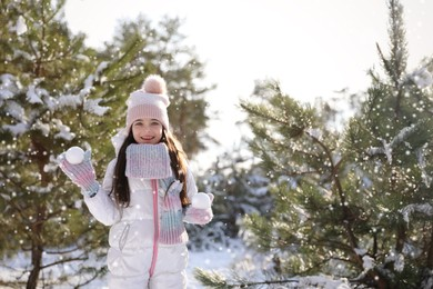Cute little girl with snowballs outdoors on winter day. Christmas vacation
