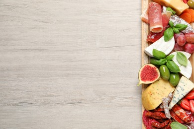Set of different delicious appetizers served on white wooden table, top view. Space for text