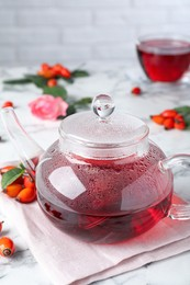 Fresh rose hip tea and berries on white marble table