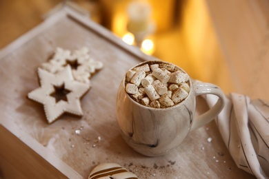 Tasty hot drink with marshmallows and cookies on wooden table