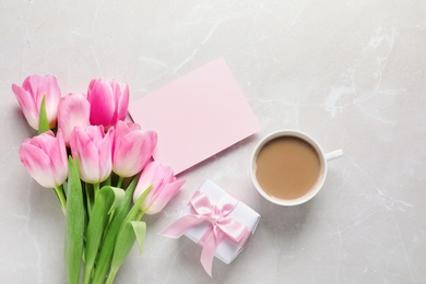 Flat lay composition of tulips and blank card on marble background, space for text. International Women's Day