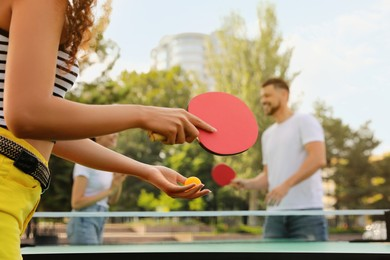 Friends playing ping pong outdoors, focus on hands
