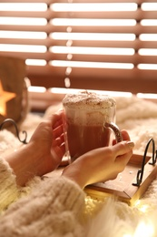 Woman holding cup of delicious drink with whipped cream indoors, closeup. Christmas celebration