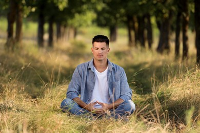Man meditating in forest on sunny day