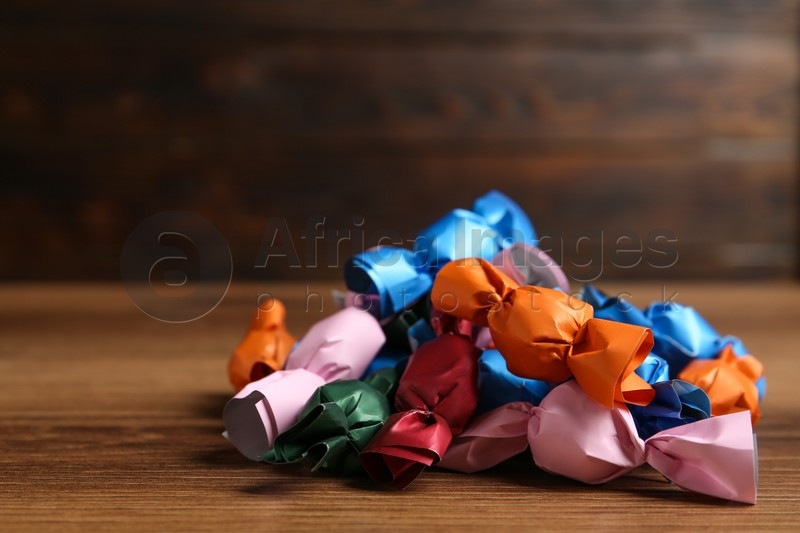 Many candies in colorful wrappers on wooden table. Space for text