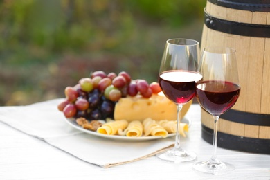 Composition with wine and snacks on white wooden table outdoors